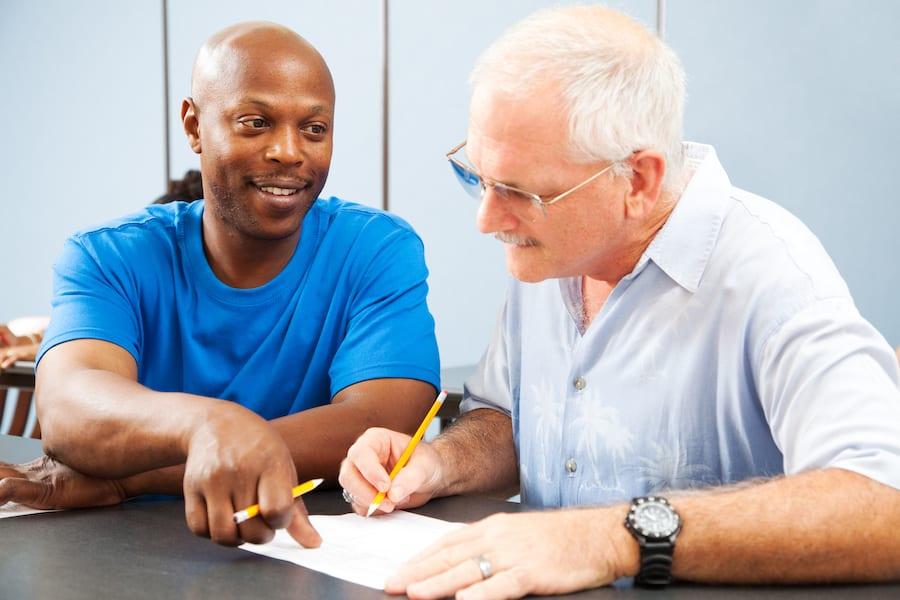 two men working together at desk smiling