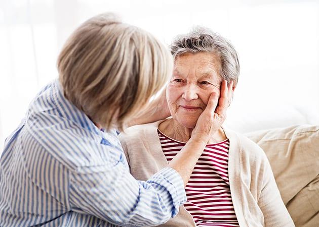 woman touching elder mother's face