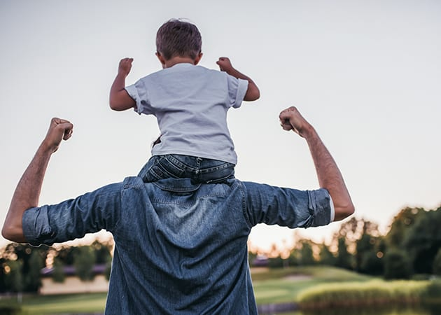 man with child on his shoulders walking around