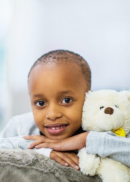 courageous kid holding onto teddy bear