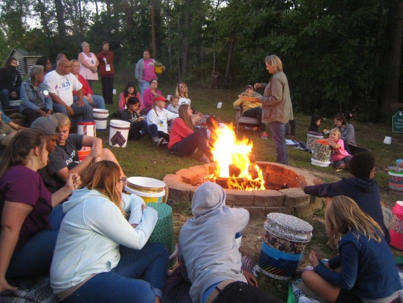 woman talking to people around campfire