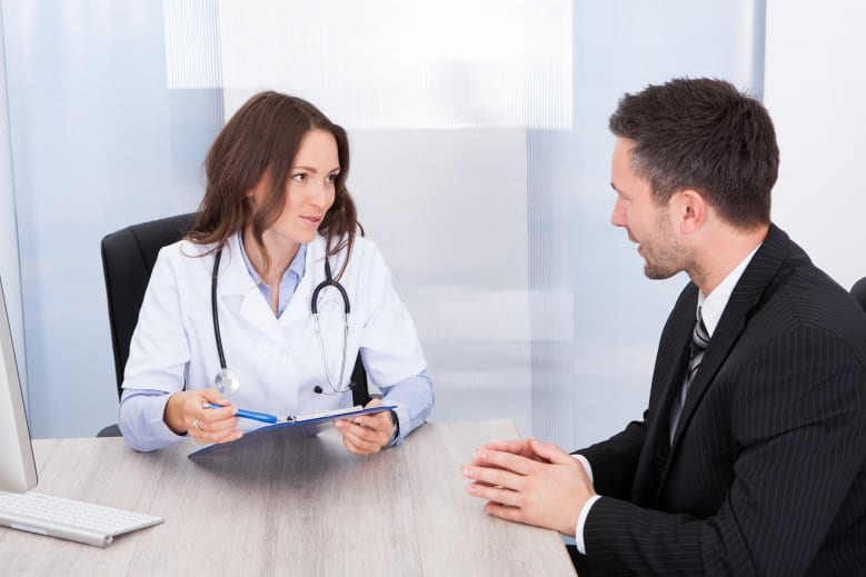 doctor talking to man in business suit