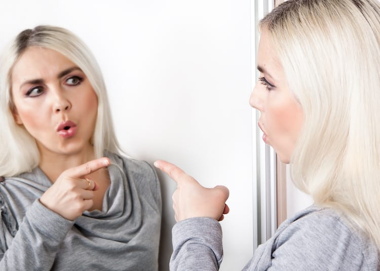 woman pointing at reflection in mirror