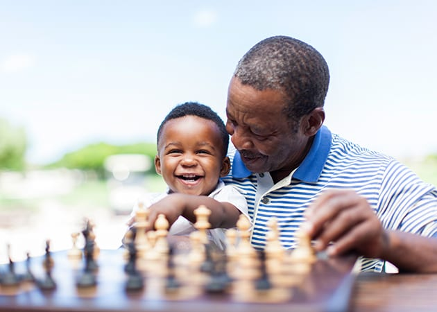Man and child smiling playing chess