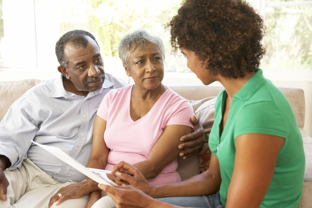 Family sitting on couch discussing something serious