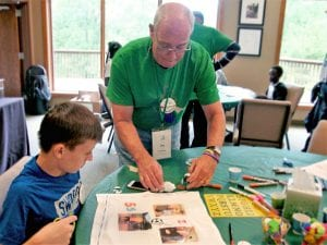 Jim Pilbean Helps a Camp Evergreen camper with a project